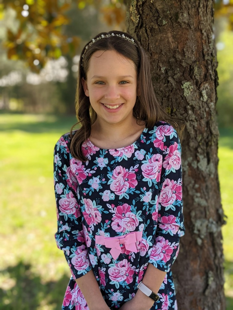 Young girl in floral print dress standing in front of a tree.